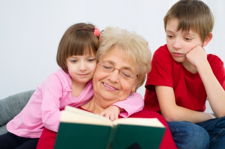 Grandmother reading a book for grandchildren at home photo