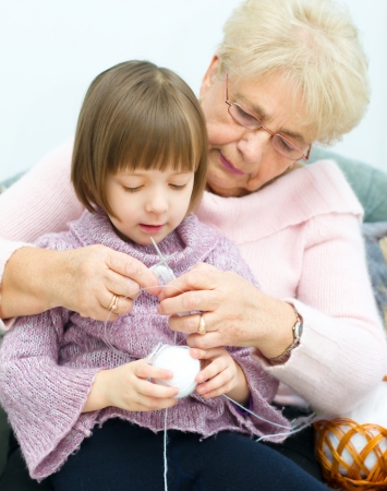 cute little girl and her granddaughter knitting together Фото со стока