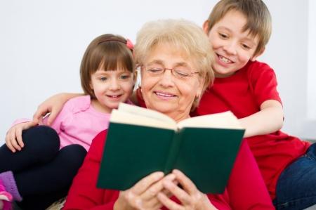 mujer hijos: Abuela que lee un libro a sus nietos en su casa