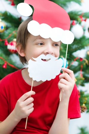 children plays with Christmas masks of Santa and deer photo
