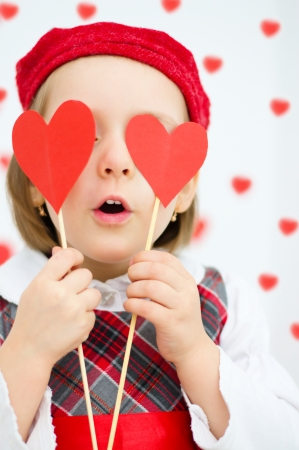 Cute happy little girl holds paper red hearts over her eyes, valentines concept