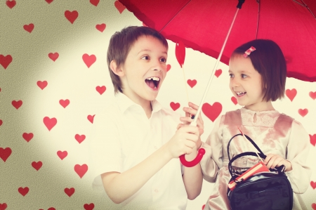Love story.Children couple under red umbrella on hearts shapes rainy background for Valentine's Day and other occasions photo