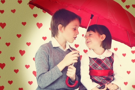 Love story.Children couple under red umbrella on hearts shapes rainy background for Valentines Day and other occasions photo