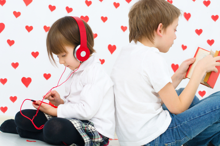 cute boy is reading a book and his sister is listening to the music Фото со стока