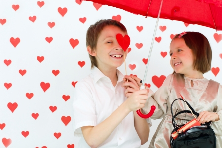 Love story.Children couple under red umbrella on hearts shapes rainy background for Valentines Day and other occasions