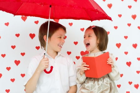 Valentines concept. Couple of happy kids reading photo