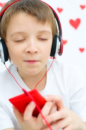 cute boy is listening to the music photo