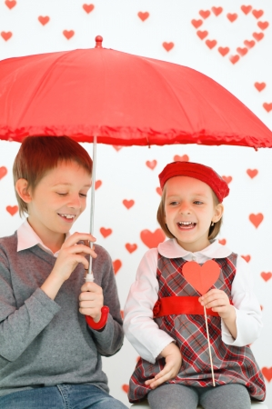 Children couple under red umbrella on hearts shapes rainy background for Valentines Day photo