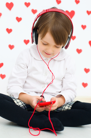 cute little girl smiling listening to the music on smart phone mobile device with headphones photo