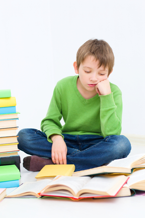schoolboy reading a book, is tired and bored photo