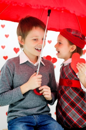 children couple under red umbrella on hearts shapes rainy background for Valentines Day and other occasions photo