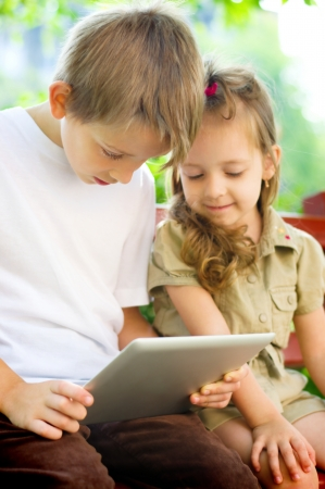 little girl with her brother using tablet computer outdoors photo