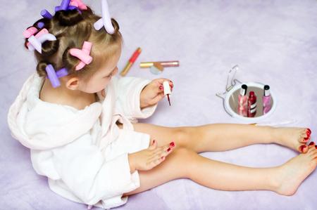 jolie petite fille: petits clous de peinture fille tout en portant des bigoudis, à la maison