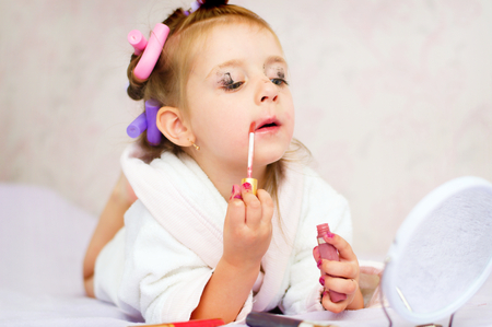 little girl painting lips while wearing hair-rollers and bathrobe