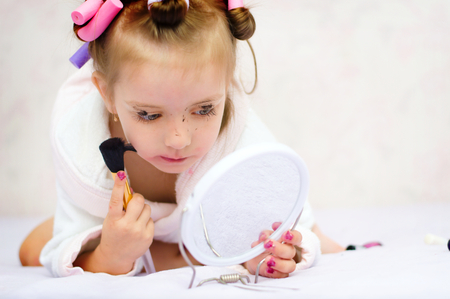 red bathrobe: little girl painting lips while wearing hair-rollers and bathrobe