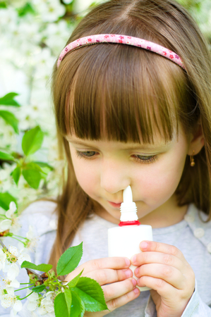 nose drops: Little girl spraying medicine in nose, nose drops, nose spray.