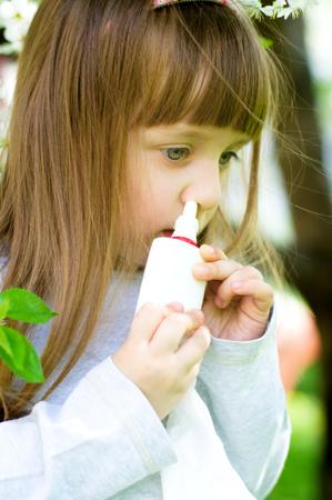 nose drops: Little girl spraying medicine in nose, nose drops, nose spray