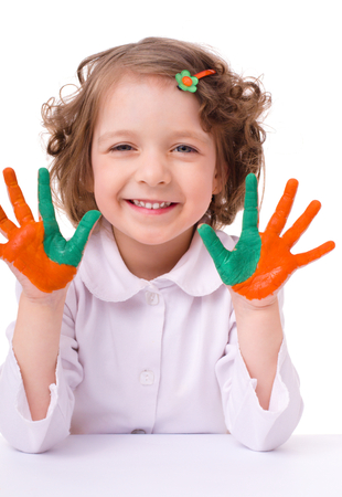 fingerpaint: cute cheerful girl showing her hands painted in bright colors, isolated over white