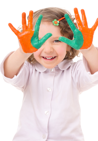cute cheerful girl showing her hands painted in bright colors, isolated over white photo