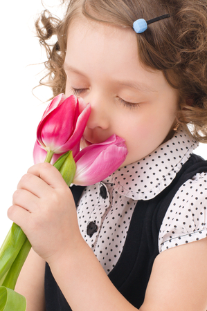 Portrait of a cute little girl smelling tulips, isolated over white