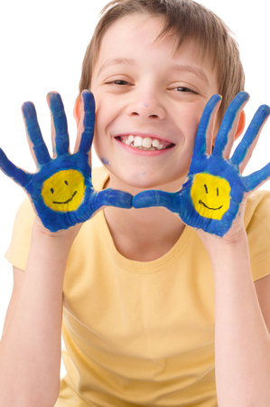Portrait of a cute boy showing his hands with painted smiling emoticons, isolated over white photo