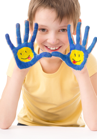 fingerpaint: Portrait of a cute boy showing his hands with painted smiling emoticons, isolated over white Stock Photo