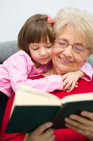 Grandmother is reading a book to her granddaughter Standard-Bild