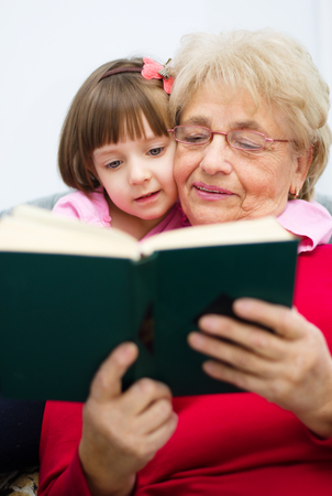 Grandmother is reading a book to her granddaughter photo