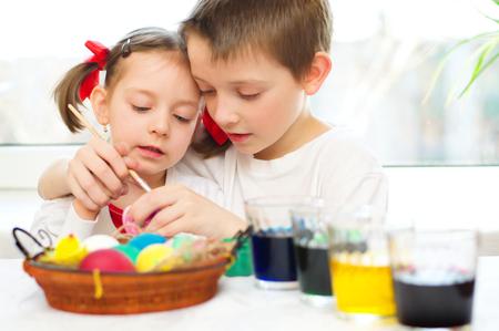hermanos jugando: niña con su hermano están coloreando los huevos para la Pascua