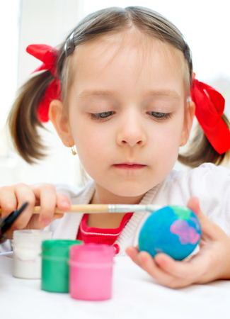 cute little girl coloring eggs for Easter photo