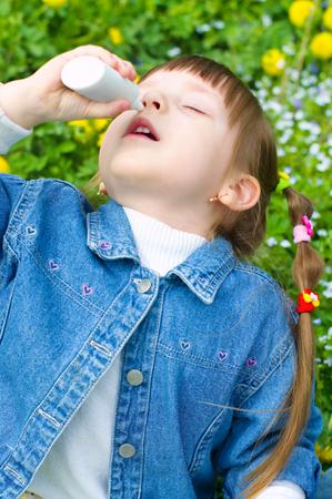 little girl spraying her nose outdoors photo