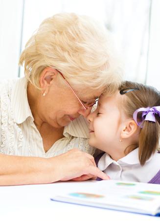 Abuela enseña a leer un libro de su nieta Foto de archivo - 26892678