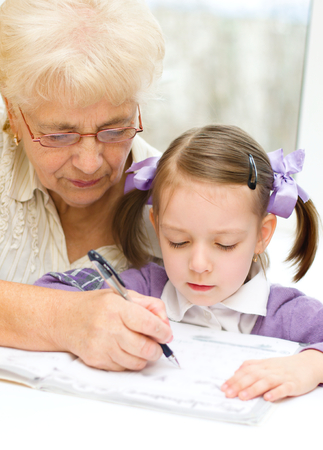 Grandmother teaches to write letters her granddaughter photo