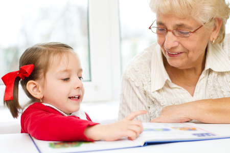 teaches: Grandmother teaches to read a book her granddaughter