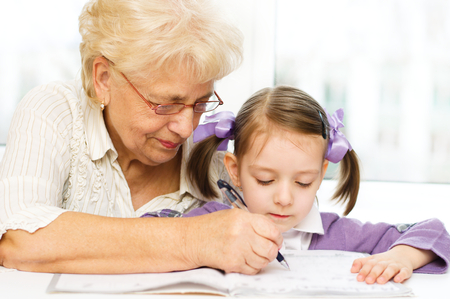 Grandmother teaches to write letters her granddaughter