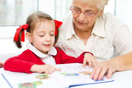 2 years old: Grandmother teaches to read a book her granddaughter