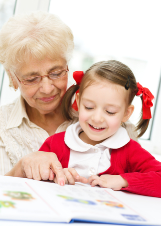 Grandmother teaches to read a book her granddaughter