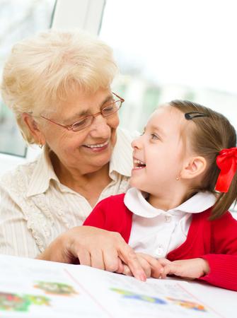 Abuela enseña a leer un libro de su nieta Foto de archivo - 27292158