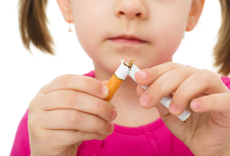 little girl is breaking a cigarette, quit smoking concept, isolated over white photo