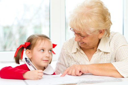 teaches: Grandmother teaches to write letters her granddaughter
