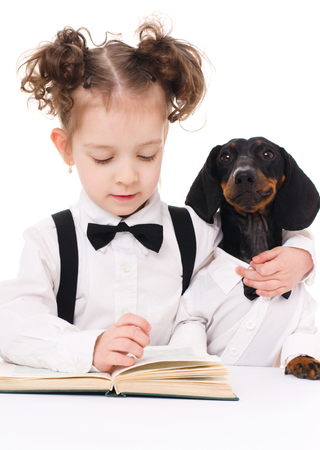 little girl with dachshund is reading a book, isolated over white photo