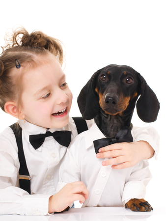 smiling little girl hugging dachshund, isolated over white photo