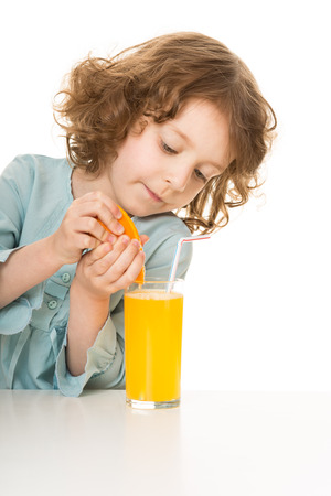cute little girl makes juice from an orange, isolated over white photo