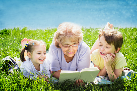 grandmother and grandson: Grandmother reading a book for grandchildren, outdoors Stock Photo