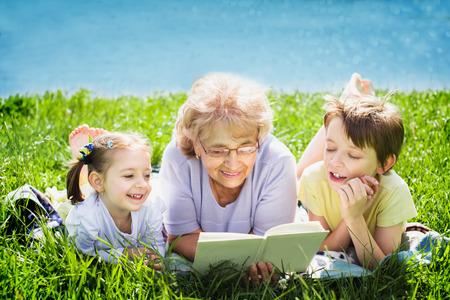 Grandmother reading a book for grandchildren, outdoors Фото со стока