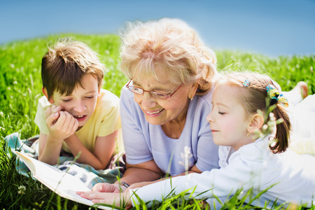 tramp: grandmother reading book to grandchildren outdoors