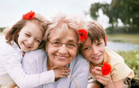 Retrato del primer verano de la abuela feliz con sus nietos al aire libre Foto de archivo