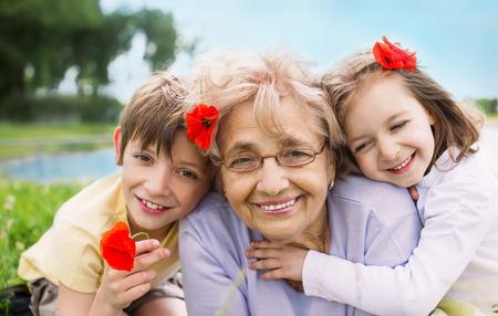 Closeup summer portrait of happy grandmother with grandchildren outdoors photo
