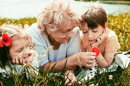 abuelos: Retrato del primer verano de la abuela feliz con sus nietos al aire libre Foto de archivo