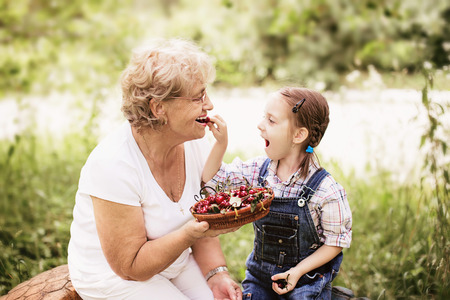great grandmother: granddaughter is feeding her grandmother with cherries in the garden Stock Photo